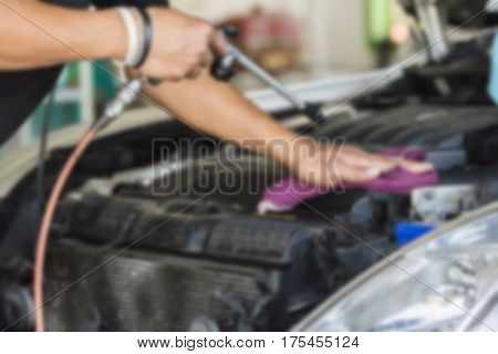 Blurry image Man was cleaning and wiping car engine with Hand Violet Microfiber Cloth and Air gun Air Pressure Car cleaning Car washing