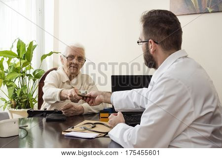Grandma pays the doctor for a visit to a private doctor's office. The patient is giving money to the doctor for a medical appointment.