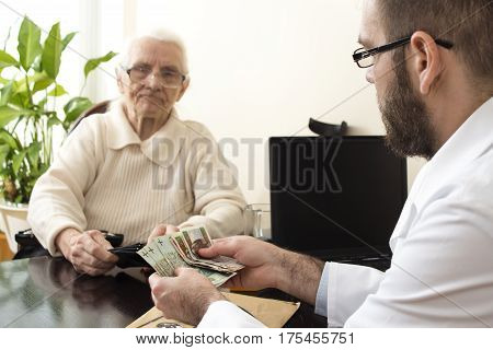 A doctor with a patient in the doctor's office. Doctor counts money.