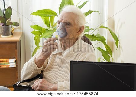 The old woman during inhaltion. The patient keeps inhaler.