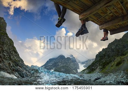 Hikers sit on a wooden flooring above the mountain valley near the glacier under Mt.Ushba. Caucasian Mountains Georgia region Svanetia.