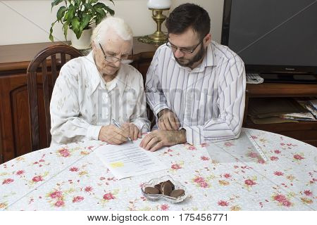 The old woman signs documents sitting at the table.Credit for the older person.The contract of donation. Credit Agreement.Grandma signs the contract documents.