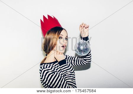 Young smiling woman on white background celebrating party, wearing stripped dress and red paper crown, happy dynamic carnival disco ball party, excited, having fun, smiling, laugh.