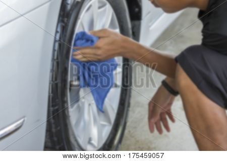 Blurry image Man was wiping car wheel with hand and microfiber cloth Car cleaning Car washing