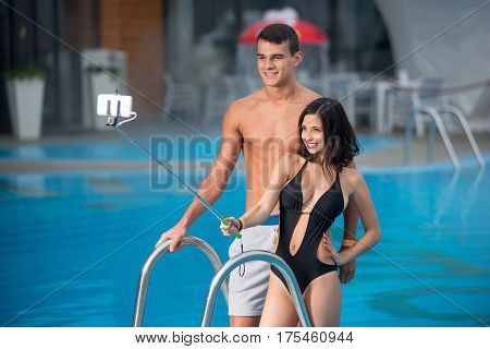 Close-up Portrait Of Young Couple With Perfect Figure Posing Against The Swimming Pool With Perfect
