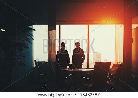 Rear view of two young businessmen near big window and work table with many armchairs in dark office having rest discussing something and looking outside after meeting metropolitan cityscape outside