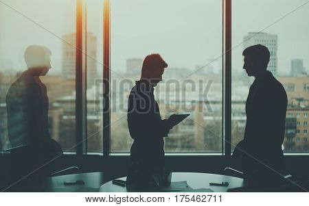 Silhouette of two businessmen: young serious boss near big window is reading quarterly report on digital tablet during private business meeting while his male colleague is waiting until he finish