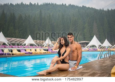 Romantic Couple Sitting On The Edge Of Swimming Pool In The Luxurious Resort. On The Background Of M