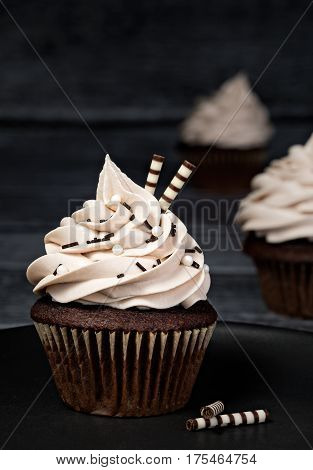 Chocolate cupcake with buttercream icing over a dark background