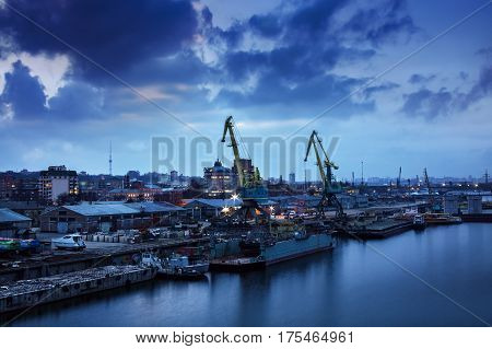 Industrial cityscape view in a harbor, blue sky background. Trucking industry near the river. River port with lighting