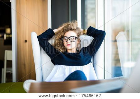 Business woman relaxing working at office desk laid back resting on chair with hands behind head. Work satisfaction businesswoman taking break after goal success or enjoying her job achievement.