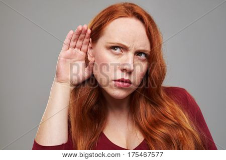 Close-up shot of young woman listening attentively to some information. Woman spying isolated over gray background