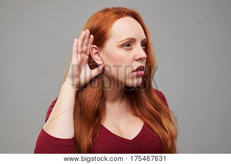 Close-up of redhead young woman holding hand near ear and trying to listen something. Female isolated over gray background