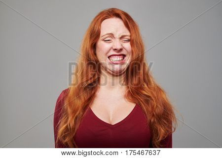 Close-up studio shot of dissatisfied woman with red hair making a grimace isolated over gray background
