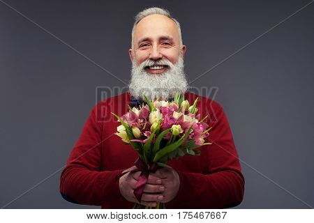 Close-up shot of handsome mature man with gray beard holding bouquet of flowers isolated over gray background