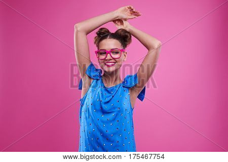 Mid shot of smiling girl with joined hands above head looking downward. Female in pink glasses and rosy lips