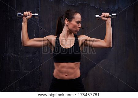 Close-up of muscular female doing biceps curl with dumbbells. Strength workout of muscular confident female doing biceps curl with dumbbells. Showing her pumped biceps, triceps and press