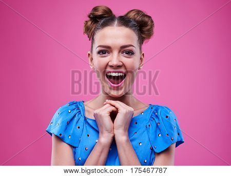 Close-up of extremely surprised woman gesturing with clasped hands. Adorable young woman opens mouth in an amazement