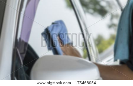 Blurry image Man was wiping car and grass with hand and microfiber cloth Car cleaning Car washing