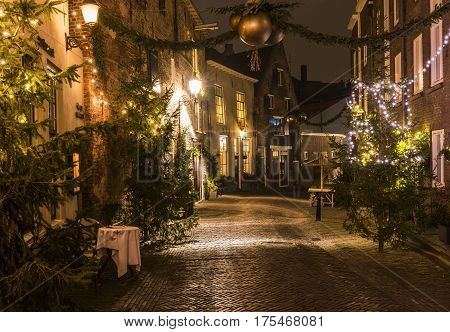 Deventer The Netherlands - December 17 2016: Roggestraat (street) in Deventer during Christmas time in the evening with christmas lights and lanterns during Dickens Festival.