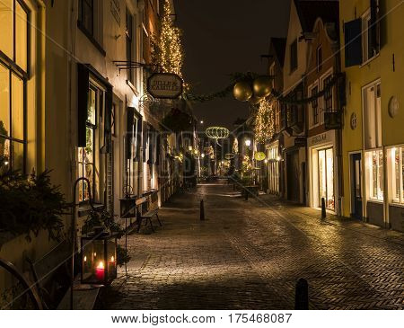 Deventer The Netherlands - December 17 2016: Walstraat (street) in Deventer during Christmas time in the evening with christmas lights and lanterns during Dickens Festival.