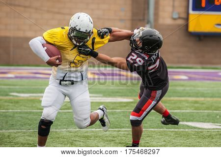 Football cornerback fighting through a stiff arm from wide receiver.