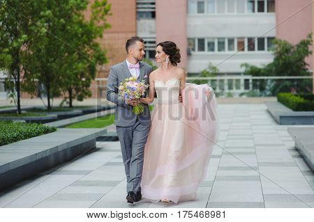 Newly married couple walk on paths holding hands and looking at each other. The building in the background. The bride and groom smiling. Bouquet in hand.