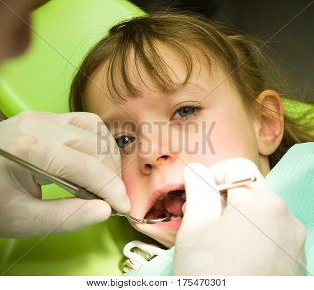 Cute little girl under prophylaxy dental examination