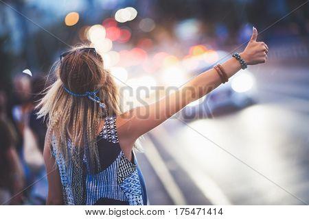 Beautiful woman hailing a cab at night while raining