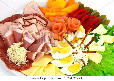 Various mixed meat and vegetable appetizers on white background.