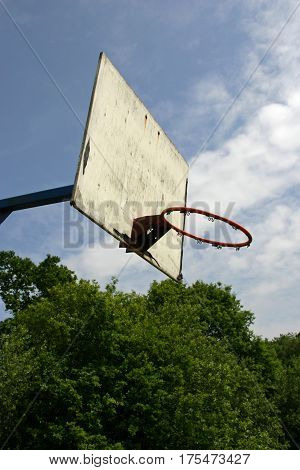 Basketball hoop with backboard but missing the net. Trees and blue sky with white cloud in the background.
