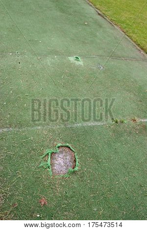 Damaged artificial cricket wicket with crease lines and holes for the stumps. Large tear in the bowling crease and smaller tear in the batting crease. Grass of the main pitch just visible to the right.