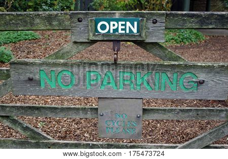 Entrance sign to park on a wooden five bar gate showing that it is open and parking and cycles are not allowed. Background of trees shrubs ground cover plants and bark mulch.