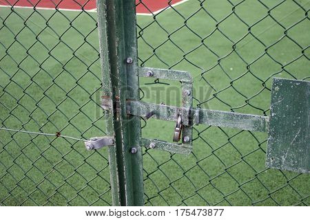 Recently refurbished and line painted tennis court viewed through chain link fencing. Locked with a green metal gate and padlock.