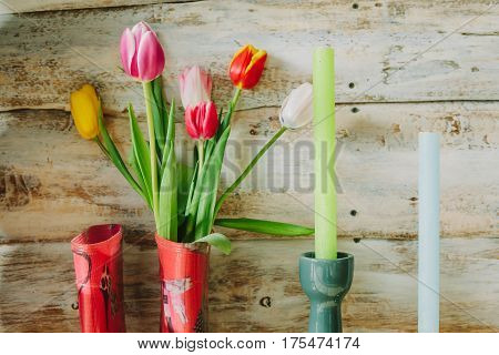wooden background with candles flowers and rain boots