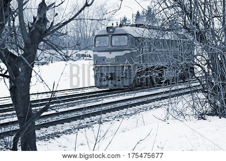 Single diesel locomotive moves across the railway tracks in wintertime cyanotype color editing