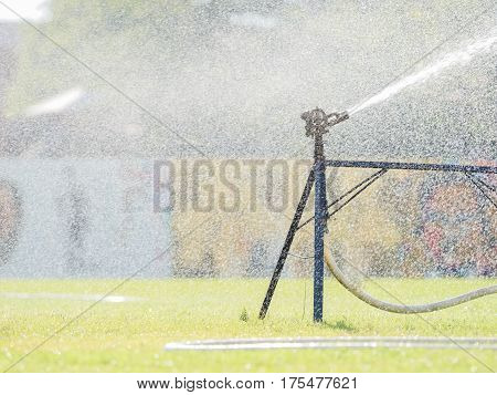 Sprinkler watering the grass of the football field