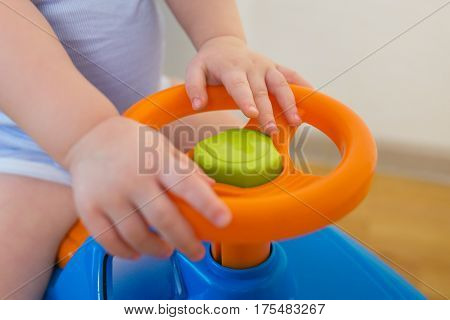 Cute Baby boy driving a toy car at home, closeup hands on rudder.