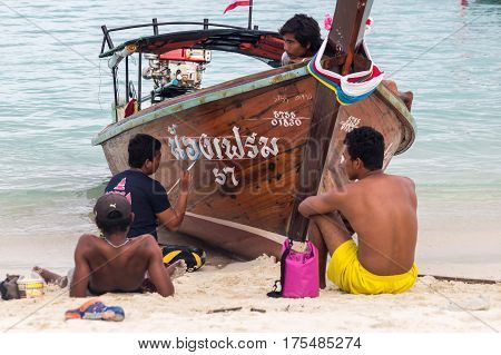 Ko Lipe, Thailand on November 10, 2016: Thai men painting a longtail boat