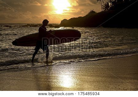 Kailua Beach, Hawaii, USA -- August 8, 2016: An unidentified surfer carrying a surfboard emerges from the ocean at sunrise.