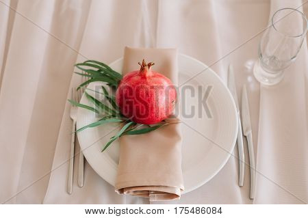 Beautifully decorated pomergranate with groom lable table sitting with nankin and dinnerware