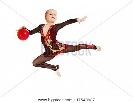 A sportive little girl jumping with a ball