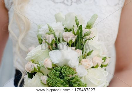 Bride holding delicate and tender marriage bouquet in white and green colours