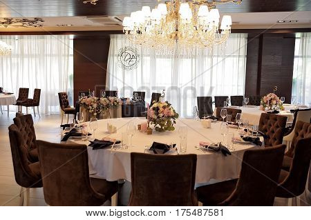 Wedding guest tables, decorated with bouquet and settings and candlesticks