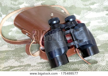 Vintage military Porro prism black color binoculars with brown leather carry case with strap on camouflage background side view close up