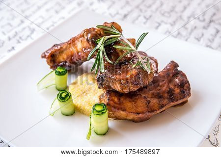 Grilled pork ribs on a white plate with cucumbers