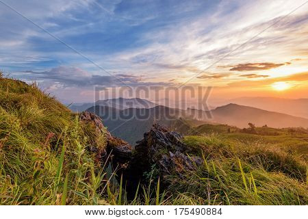 Beautiful landscape nature on peak mountain with sun cloud fog and bright colors of sky and sunlight during sunset in winter at viewpoint Phu Chi Fa Forest Park in Chiang Rai Province Thailand