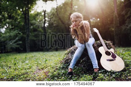 Heartbroken Woman In Nature With Guitar