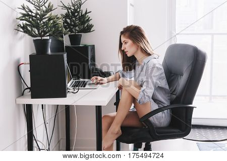 Portrait of young beautiful Caucasian girl woman student in pajamas shirt working on laptop computer sitting in office chair at home browsing internet drinking coffee early morning lifestyle