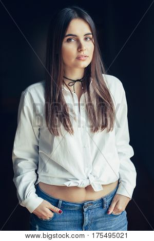 Portrait of pensive sad white Caucasian brunette young beautiful girl woman model with long dark hair and brown eyes in white shirt tied in a knot blue jeans looking in camera on black background